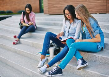 Modern teen girls reading book while sitting on stairs on background of another student
