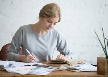 Student female performing a written task in a copybook with a pen, looking at the textbook, education concept photo, horizontal